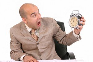 businessman looking at clock alarm